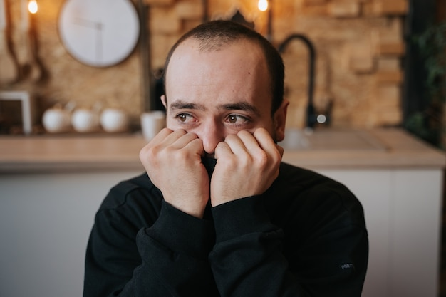 Eenzame trieste knappe man lijdt aan depressie en eenzaamheid, in de keuken in huis, binnen