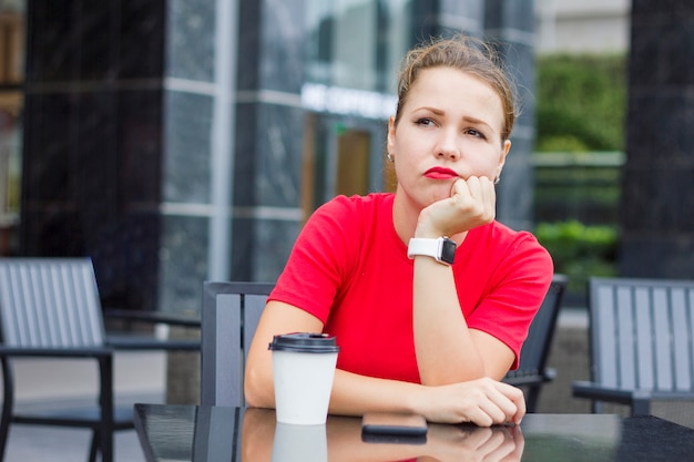 Eenzame trieste peinzende gefrustreerde vrouw zit in een cafe, buitenshuis met een kopje koffie, verveeld, wachtend op een date met een late man. vriend kwam niet naar de vergadering, vergeten boos dame.