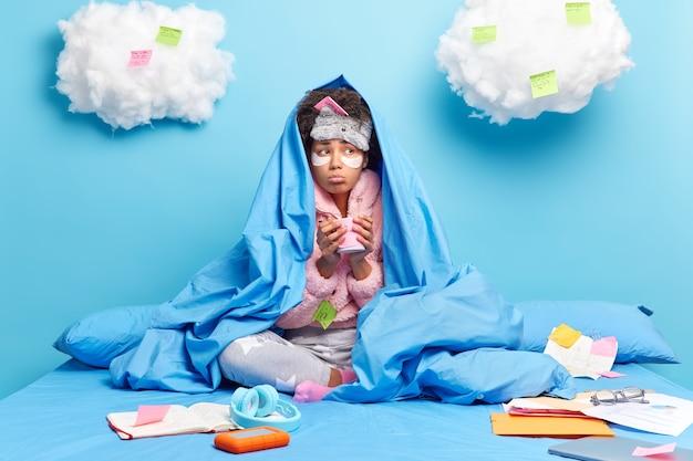 Eenzame trieste vrouw met zich meebrengt onder deken drinkt warme drank