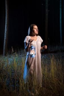 Eenzame verloren vrouw in bos 's nachts wandelen met kaarslantaarn