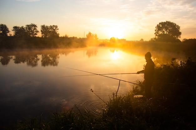 Eenzame visser vissen op mistig meer in de vroege ochtend net na gouden zonsopgang.