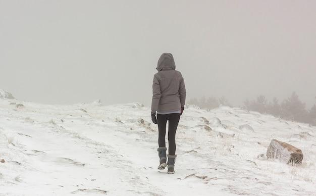 Eenzame vrouw die in de sneeuw loopt. extreem weer in de winter. in het nationaal park sierrra de guadarrama, madrid en segovia.