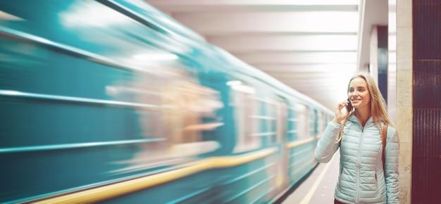 Eenzame vrouw die metro kijkt. snelheid elektrische trein op een platform in de metro. meisje praten aan de telefoon in de metro