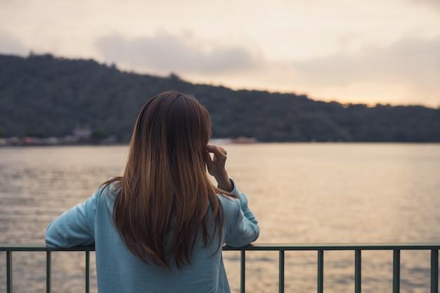 Eenzame vrouw die zich afwezig bij de rivier bevindt