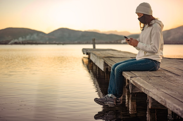 Eenzame vrouw gebruikt haar smartphone om het laatste nieuws over covid-19 te volgen, zittend op een pier met beschermend masker bij zonsondergang of zonsopgang.