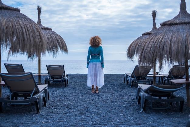 Eenzame vrouw gezien vanaf de achterkant staat in het midden van lege stoelen en parasols die wachten en kijken naar de stille oceaangolven. concentratie en vrijheid alternatief levensstijlconcept buiten