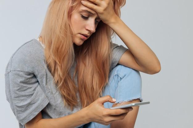 Eenzame vrouw in depressie kijken naar telefoon krijgt slecht nieuws. relaties, ruzie