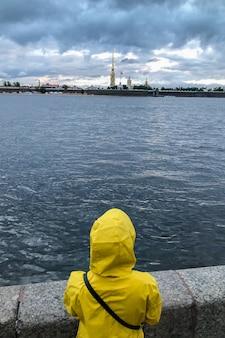 Eenzame vrouw in gele regenjas en capuchon staande op de dijk