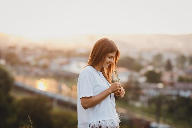 Eenzame vrouw in wit shirt staat met een veld bloem