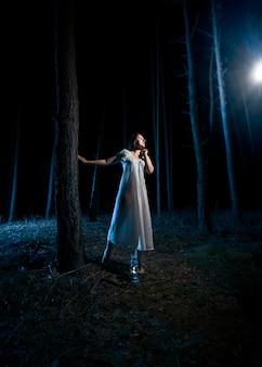 Eenzame vrouw in witte nachtjapon die 's nachts naar de lichtstraal kijkt