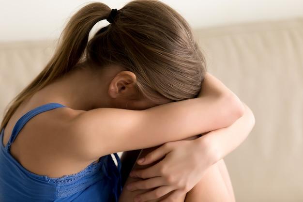 Eenzame vrouw knuffelen knieën en huilen