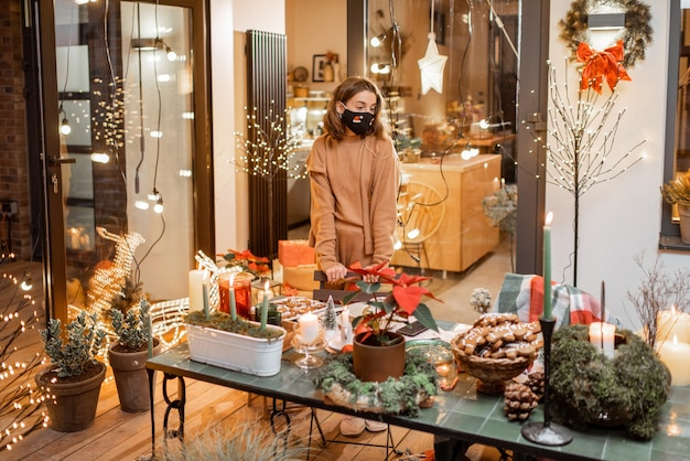Eenzame vrouw met gezichtsmasker tijdens de nieuwjaarsvakantie thuis op het prachtig ingerichte terras. concept van quarantaine en zelfisolatie tijdens de epidemie op feestdagen