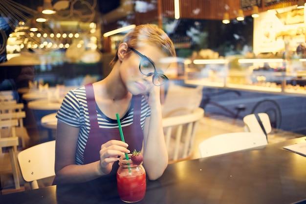 Eenzame vrouw zittend aan de tafel met cocktail ontspannen in een café