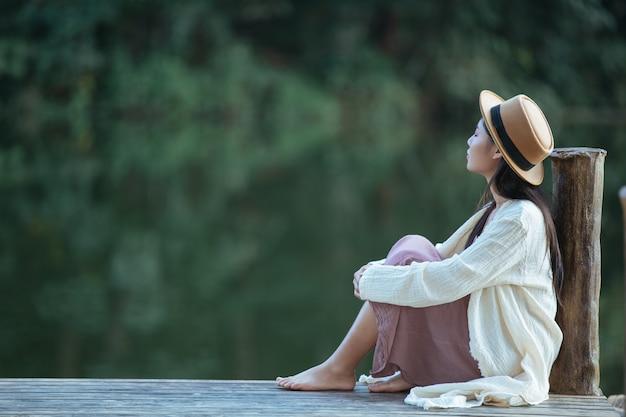 Eenzame vrouw zittend op de waterkant vlot
