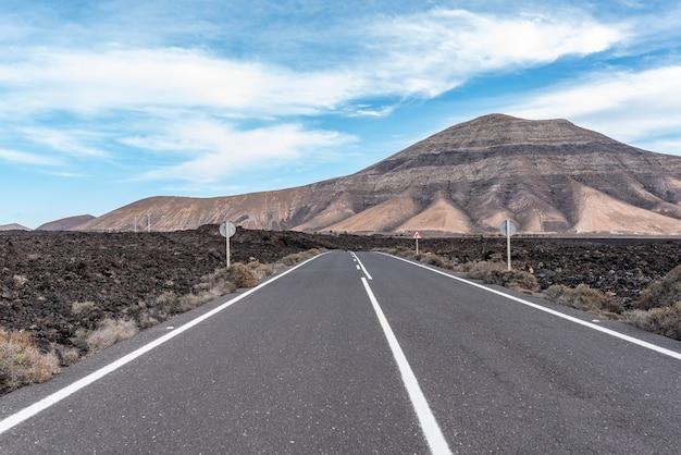 Eenzame weg midden in het woestijnlandschap van lanzarote.