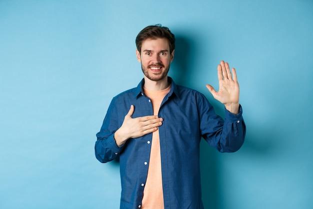 Eerlijke jonge man glimlachend en belofte doen, hand op hart en arm omhoog houden, beloven of eed afleggen, zweren de waarheid te vertellen, staande op een blauwe achtergrond.