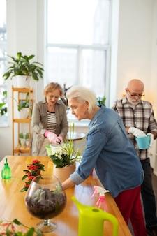 Eerste. aardige oudere vrouw die een bloem neemt terwijl ze in de grotere bloempot wil doen