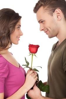 Eerste afspraakje. vrolijk jong liefdevol stel dat een rode roos vasthoudt en glimlacht terwijl ze oog in oog staan en geïsoleerd op een witte achtergrond