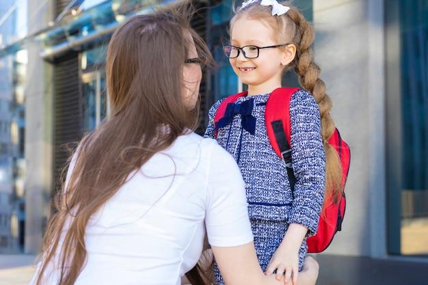 Eerste dag in de herfst. terug naar schoolkinderen. moeder leidt klein schoolmeisje in uniform, schooltas in het eerste leerjaar. begin van de lessen. kind zwaai een hand naar moeder. ouder ontmoet schoolkinderen