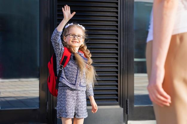 Eerste dag in de herfst. terug naar schoolkinderen. moeder leidt klein schoolmeisje in uniform, schooltas in het eerste leerjaar. begin van de lessen. kind zwaai een hand naar moeder.