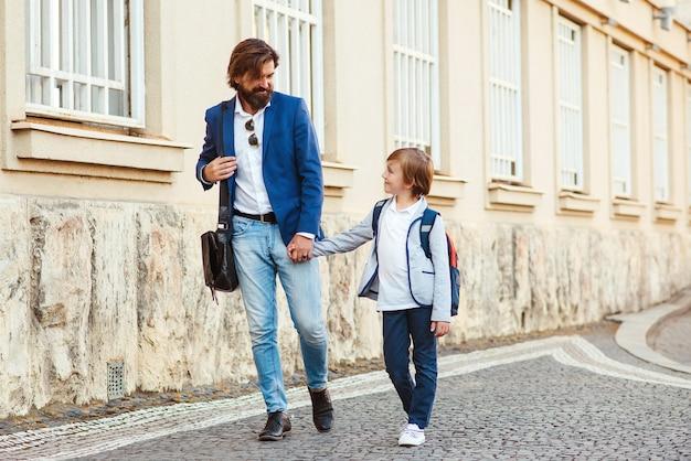 Eerste dag op school. vader leidt een zoon in de eerste klas. vader met kind hand in hand op straat. terug naar school concept.