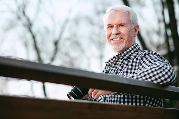 Eerste foto. lage hoek van positieve volwassen man met behulp van camera en glimlachen naar de camera