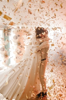 Eerste huwelijksdans van pasgetrouwd. gelukkige bruid en bruidegom dansen onder gouden confetti
