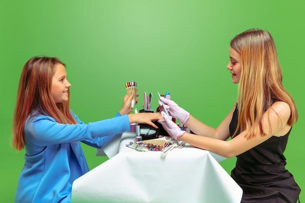 Eerste klant. meisje droomt van beroep van nagelskunstenaar. jeugd, planning, onderwijs, droomconcept. wil succesvolle werknemer worden in de mode- en stijlindustrie, manicurekunstenaar.
