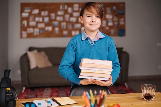 Eerste klas jongen die thuis studeert, een stapel boeken vasthoudt, zich klaarmaakt voor online les
