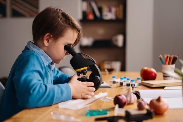 Eerste klas jongen thuis studeren met behulp van de microscoop