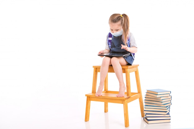 Eerste-klasser in medisch masker leert lezen. klein meisje op thuis afstandsonderwijs. kind in medische masker werkt op laptop en boeken. huiswerk aan het maken.