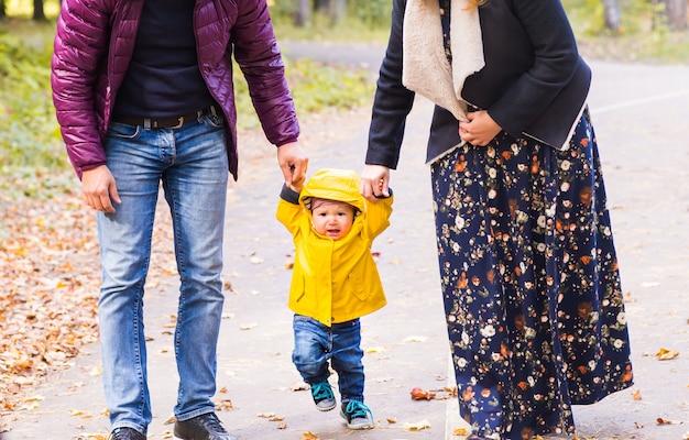 Eerste kleine jongensstappen met moeder en vader