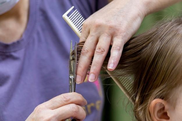 Eerste knipbeurt voor een jong meisje. gespleten haarpunten knippen met een schaar.
