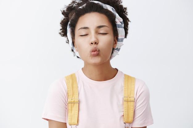Eerste kus nooit vergeten. portret van charmante en tedere stijlvolle vrouw met donkere huid in hoofdband en gele overall over t-shirt, ogen sluiten en lippen vouwen