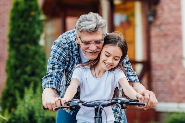 Eerste lessen fietsen. knappe grootvader leert zijn kleindochter fietsen. dichtbij huis oefenen.