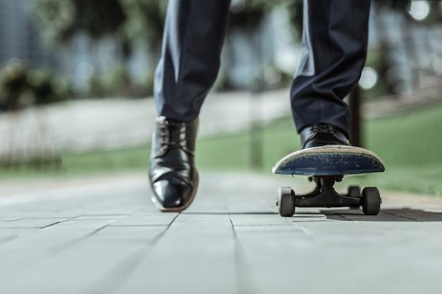 Eerste poging. close-up van mannelijke voeten staande op blauwe skateboard tijdens het rijden erop