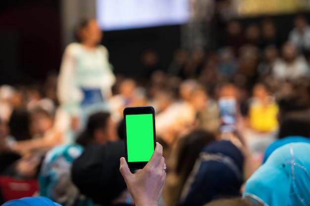 Eerste rij vip-gasten mensen uit het publiek filmen vdo modeshow met mobiele smartphone