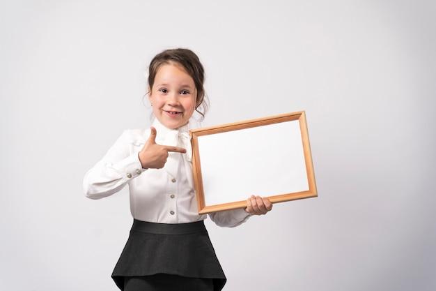 Eerste school meisje houdt een wit laken voor de inscriptie