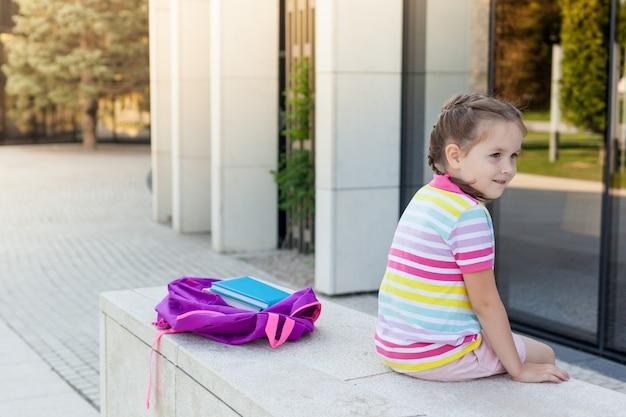 Eerste schooldag. leerling van basisschool met in hand boek. meisje met een rugzak dichtbij het gebouw openlucht.