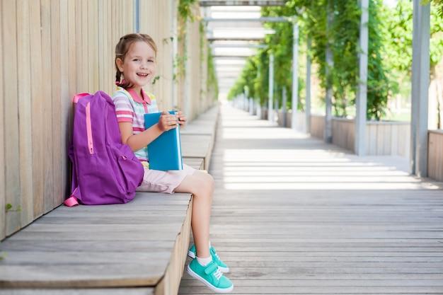 Eerste schooldag. leerling van de basisschool met boek in de hand. . meisje met een rugzak dichtbij het gebouw openlucht. begin van lessen. de eerste dag van de herfst. concept terug naar school.