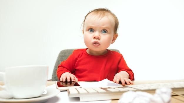 Eerste sms. kind babymeisje zit met toetsenbord van moderne computer of laptop in het wit