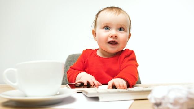 Eerste sms. kind babymeisje zit met toetsenbord van moderne computer of laptop in witte studio