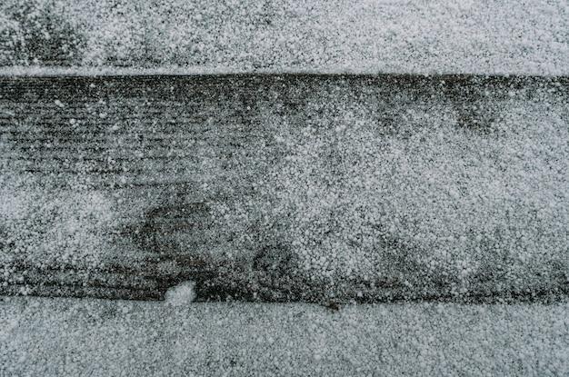 Eerste sneeuw op een bleek, vervaagd bruin en koelblauw geregenereerd grenenhouten oppervlak met verouderde planken op een rij
