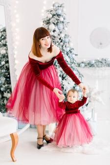 Eerste stapjes van een klein meisje, met moeder, haar ondersteunen, plezier maken tijdens het vieren van kerstmis