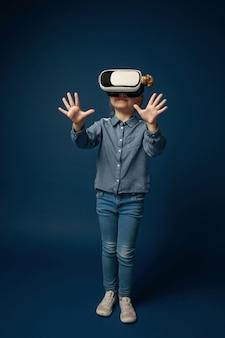 Eerste stappen in sprookjes. klein meisje of kind in spijkerbroek en shirt met virtual reality headset bril geïsoleerd op blauwe studio achtergrond. concept van geavanceerde technologie, videogames, innovatie.