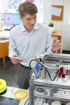 Eerste stappen. knappe jongeman oefenen met het gebruik van 3d-printer terwijl hij een tablet vasthoudt met een handleiding erop