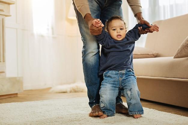 Eerste stappen. leuke kleine jongen met donkere ogen die naast de bank staat en leert lopen terwijl zijn afro-amerikaanse papa zijn handen vasthoudt