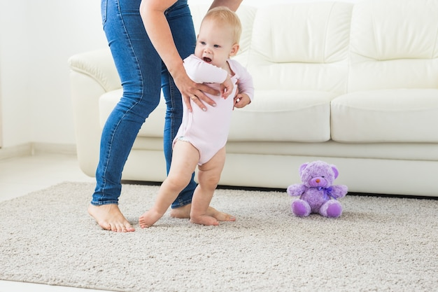 Eerste stappen van baby peuter leren lopen in witte zonnige woonkamer schoeisel voor kind