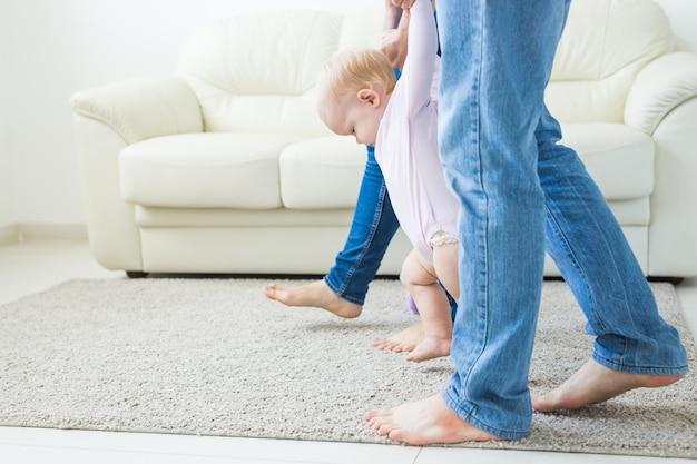 Eerste stappen van baby peuter leren lopen in witte zonnige woonkamer. schoeisel voor kinderen.