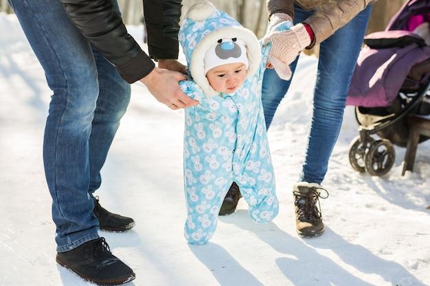 Eerste stappen van een baby in de winterpark.